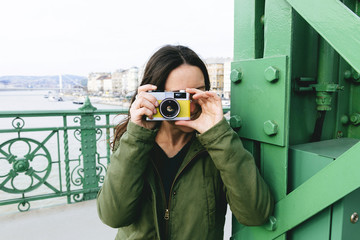 Hungary, Budapest, Young woman on Liberty bridge taking pictures