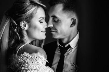 Romantic happy couple, bride & groom kissing near window closeup b&w