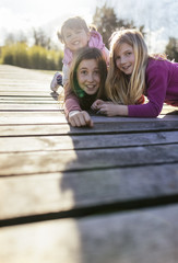 Group picture of three girls on a boardwalk pulling funny faces