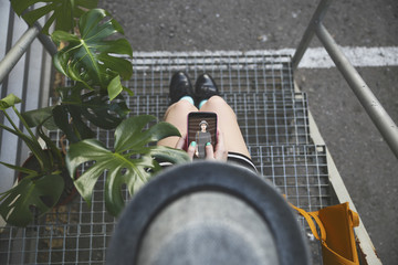 Top view of woman sitting on stairs holding smartphone with her own photography