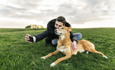 Man taking selfie with his dog on meadow