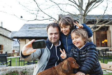 Father taking a selfie with his sons and the dog with smartphone