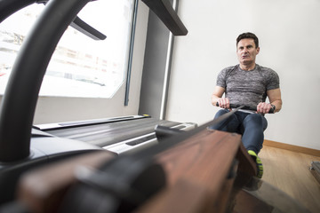 Mature man exercising at rowing machine in gym