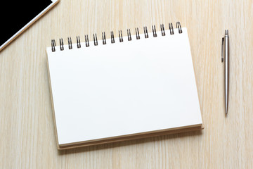 Top view Notebook with blank sheet and pen on wooden table