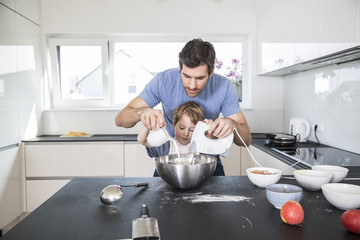 Father and son preparing waffle dough in kitchen