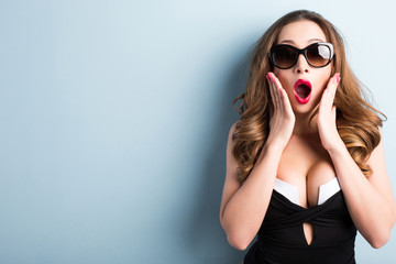 Sexy woman in sunglasses with facial expression of surprise close-up.