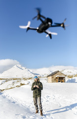 Man flying drone in snowy mountains