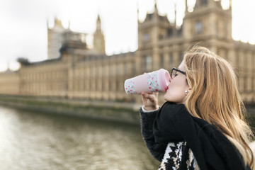 UK, London, young woman drinking coffee in front of Palace of Westminster