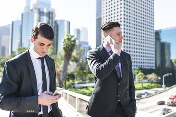 USA, Los Angeles, two businessmen using cell phones