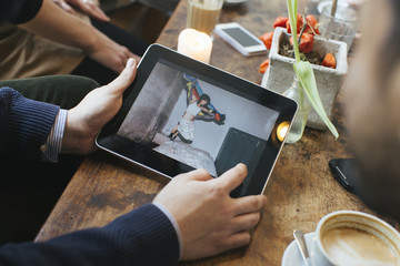 Man in a cafe showing picture on digital tablet to friends