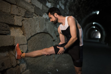 Runner doing stretching exercise in a tunnel