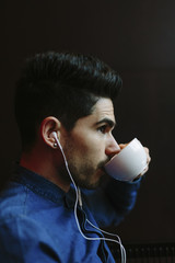 Profile of young man wearing earphones while drinking coffee