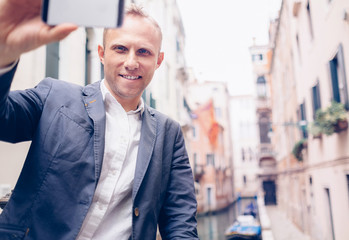 Smiling man take a selfie tourist photo on the Venice chanel bac