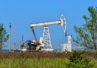 Old oil pumpjack on the summer field