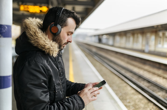 Man with headphones standing on platform using his smartphone