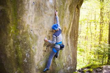 The girl climbs on the rock.