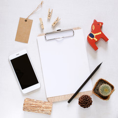 Blank clipboard and smartphone with cute decorated on workspace
