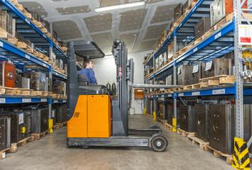 Warehouse worker driving forklift in storage for machine blocks