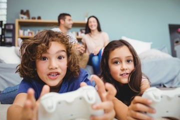Cheerful siblings with controllers playing video game at home