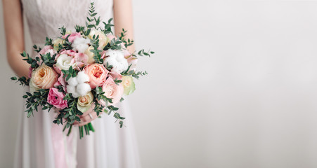 Beautiful wedding bouquet in hands of the bride. Peony rose, cotton, roses. Pink and Peach. Trendy and modern wedding flowers. Ideal photo for commercial. Space for your logo