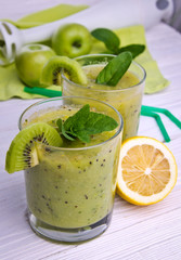 Green smoothie with mint and fruits on the wooden background