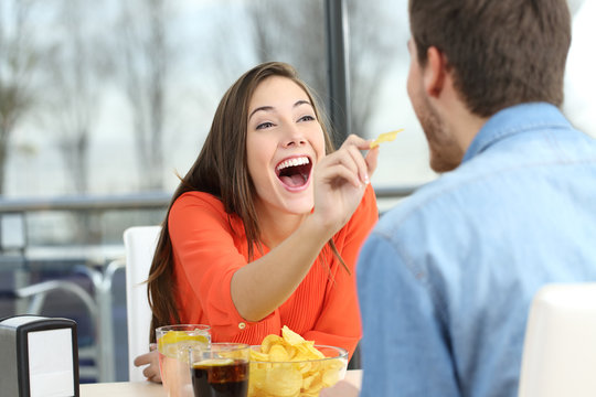 Playful couple eating chip potatoes