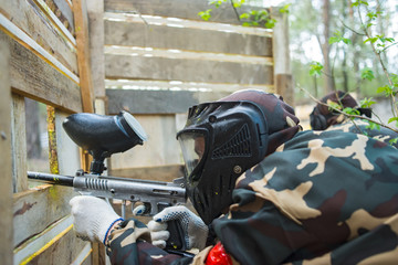 Man in a protective mask with a gun to play paintball in the woods in summer