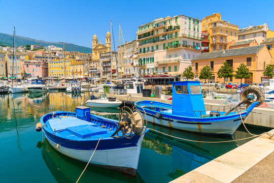 Traditional fishing boats in Bastia port on sunny summer day, Corsica island, France