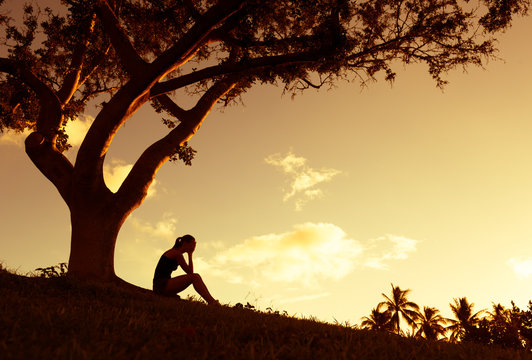 Sad young woman sitting outdoors under a tree.