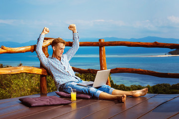 Young successful man sitting with laptop at mountain restaurant