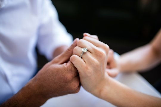 Close-up of couple holding hands with engagement ring
