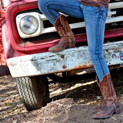 Western style image of cowgirl's legs in jeans and boots and old Texas truck on background