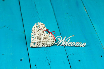 Heart and word welcome on teal blue background