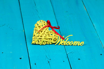 Yellow heart and welcome sign on teal blue background