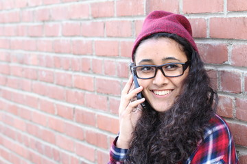 Smiling Winter Hipster Girl in Plaid Shirt and Beanie Hat with Mobile Phone Isolated on Brick Wall. Teenage Communication Concept.