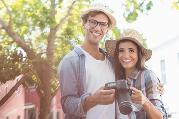 Portrait of young couple holding camera