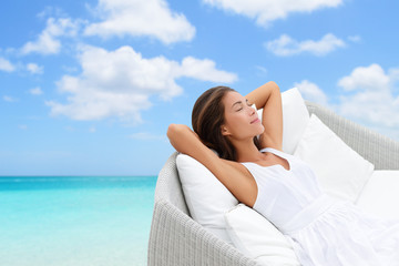 Sleeping woman relaxing lounging on white outdoor sofa day bed lounger on beach ocean background. Asian girl lying down laid back on pillows dreaming or enjoying the sun carefree happy. Ho