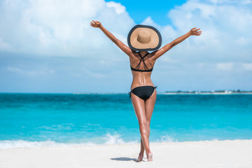 Summer vacation happiness carefree joyful sun hat woman with open arms in success enjoying body weight loss tropical beach destination. Holiday bikini girl relaxing from behind on Caribbean vacation.