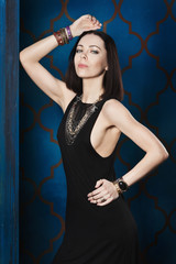 Gorgeous dark-haired woman in a black evening dress and luxurious golden jewelry. Oriental palace, a dark blue wall with gold pattern. Morocco, night, luxury, pleasure.