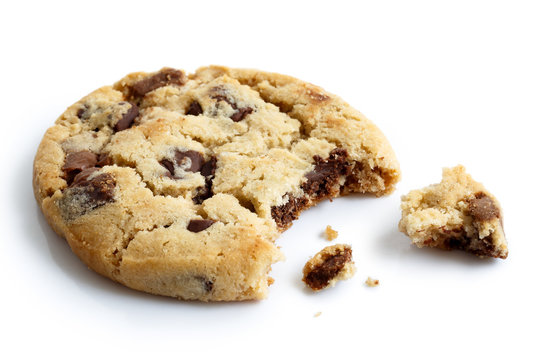 Single light chocolate chip cookie, bite missing with crumbs, is