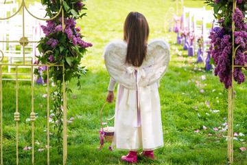 Little girl in white dress and angel wings holds basket of petals on wedding ceremony. Back view