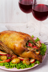 Roast duck with potato, apples, salad, thyme and rosemary. Two glasses of red wine