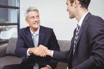 Smiling businessmen handshaking