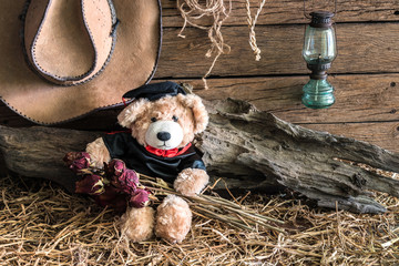 Teddy bear holding dry red roses in barn background