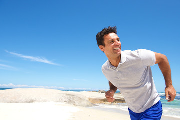 Cheerful middle aged man running on the beach