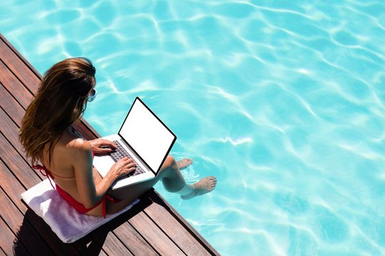 Woman using her laptop on the pool edge