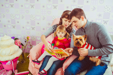 Young family is reading a book with a daughter