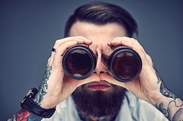 Bearded hipster man holding beer bottles like binocular. Fototapete