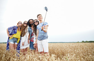 hippie friends with smartphone on selfie stick
