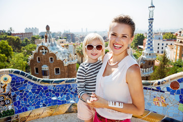 Smiling mother and baby spending fun time at Park Guell
